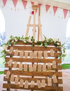 exemple de diy mariage plan de table en palette de bois et étiquettes en papier krafts, noms invités écrits en noir, chevalet comme support