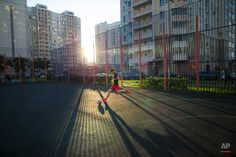 """In this July 2, 2015 photo, a teenager plays soccer in the last rays of the setting sun at a playground in Moscow, Russia. While the Brazilians learn to play on the streets or the beach, Russian children have the """"dvor,"""" the yard space between towering apartments blocks. Yard football is a national tradition, and the asphalt pitches are often the first step in the careers of future stars of the Russian national team. (AP Photo/Alexander Zemlianichenko) Football Pitch, Football Field, Tower Apartment, The Allure, Play Soccer, Story Inspiration, Playground, Fields, Street View"""