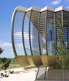 A row of aluminium ribs curves away from the serrated glass facade of this research laboratory.