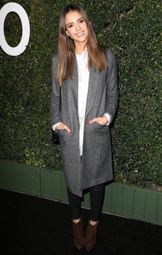 Jessica Alba in a white tunic top, long gray coat, skinny jeans and booties