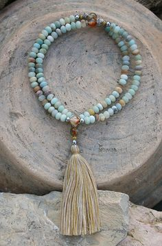 Mala made of 108, 6 x 8 mm - 0.236 x 0.315 inch, beautiful frosted amazonite gemstones and decorated with faceted agate, hematite, silver and gold color beads and with a tassel. The Mala has a total length of approximately 69 cm - 27.17 inch.