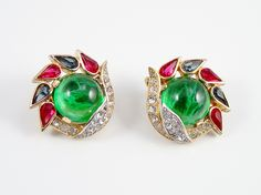 A lovely pair of vintage rhinestone earrings by Trifari.From the jewels of India line, the earrings have green cabachon glass stones surrounded by blue and red pear shape rhinestones and clear pave rhinestones.