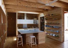 The almost-entirely tallowwood kitchen is custom. Muuto pendant lights, bar stools by Alvar Aalto for Artek, a Vola faucet, and a ceiling fan by Beacon Lighting finish the room. Tagged: Kitchen and Medium Hardwood Floor. Photo 6 of 9 in Local Wood Clads Every Surface of This Idyllic Australian Getaway