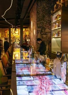 Miss Ko, Paris - Philippe Starck designed the 26-metre table of digital screens running through the restaurant glowing with Asian news channels