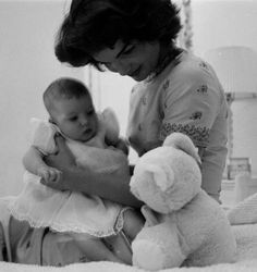 Jackie Kennedy showing her daughter a teddy bear. She is in Caroline's nursery at their Georgetown home.