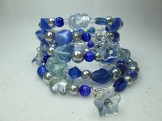 AN ELEGANT, ART DECO, HANDMADE BRACELET.  THIS EXQUISITE BANGLE BRACELET WAS CREATED USING VARIOUS HUES OF BLUE GLASS BEADS, STERLING SILVER PLATE TUBES, CLEAR SWAROVSKI CR...