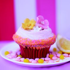Our June Cupcake of the Month: RAVISHING RASPBERRY LEMONADE: Raspberry flavored cake with a lemon curd filling, creamy raspberry frosting, decorated with pink & yellow sugar crystals and topped with a candy flowers.