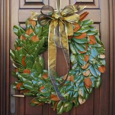 For Simplicity's Sake: The holidays bring enough stress as it is. Keeping a wreath basic can alleviate decorating worries without forgoing a classy entrance. A Southern magnolia's broad, glossy green leaves create contrast with the door's wood. Flip some leaves to their brown sides to add texture. One large gold bow adds flair, while serving as the hanger. Ribbon available at craft supply stores.