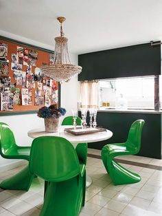 12 Ways to Use Panton Chairs: Four green Panton style chairs surround a dining table over which hangs an ornate chandelier, in genius contrast, proving these modern icons work well with eclectic interiors too.