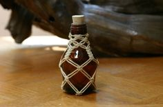 A small dark colored bottle decorated with white macrame.