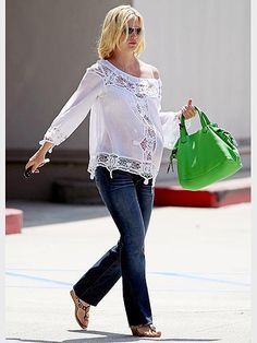 January Jones effortlessly sexy maternity style- breathy white top with flared jeans and sandals.