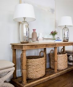Beige x-stools flank a reclaimed wood console table fitted with a shelf holding . Beige x-stools flank a reclaimed wood console table fitted with a shelf holding seagrass baskets an Entryway Console Table, Entry Tables, Entryway Decor, Pottery Barn Entryway, Sofa Tables, Console Table With Mirror, Entryway Ideas, Entrance Ideas, Pottery Barn Baskets