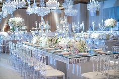Crystal chandeliers hung above long mirrored tables adorned with lush floral arrangements and candelabras highlighted with blue uplighting by @thelightersidela. || Venue: @fairmontgranddelmar | Planning  Design: @internationaleventco | Florals: @marksgarden @michael_MarksGarden | Lighting: @thelightersidela | DJ: @liventgroup | Photographer: @jessicaclaire | Videographer: @davidmedillproductions | Rentals: @palacepartyrental | Cake: @jandlcakes