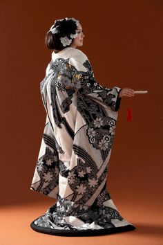 Uchikake is a highly formal kimono worn only by a bride or at a stage performance. The Uchikake is often heavily brocaded and is supposed to be worn outside the actual kimono and obi, as a sort of coat. One therefore never ties the obi around the uchikake. It is supposed to trail along the floor, this is also why it is heavily padded along the hem. The uchikake of the bridal costume is either white or very colorful often with red as the base colour.