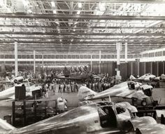 Interior of the Curtiss-Wright factory showing the twin-engine Curtiss AT-9 and the A-25 Helldiver airplanes under construction. (1941)
