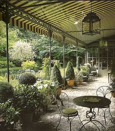 // love the garden beyond and the feeling underneath the awning, the lightness of the gravel, the delicate chairs and table