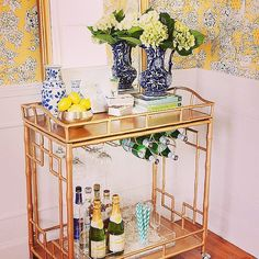 Gold and Glamorous: Between the gold cart, barware, and flowers, this setup is picture perfect. Not only is it beautiful and decorative, but it also has all the elements needed to entertain at a moment's notice!  Source: Instagram user societysocial