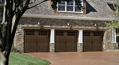 "The ""Classica™"" Collection from Banko Overhead Doors. Dark wood stand out against a stone home."