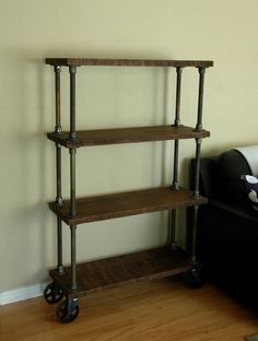 Industrial Bookshelf: Unique custom made 4 tier bookcase on heavy duty 5? cast iron caster wheels. he entire piece is aged to look mid-century and was inspired by the French industrial era. It disassembles pretty easy for shipping.