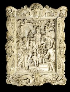 A 19th century Dieppe ivory relief of The Felicity of the Regency of Marie de' Medici after Sir Peter Paul Rubens depicting Marie as the personification of Justice flanked by Cupid, Minerva, Prudence, Abundance, Saturn and two figures of Pheme, within an ornate ivory frame carved with scrolling acanthus leaves, grotesque heads, garlands of fruits and surmounted by a female mask, with a bearded male mask below