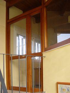Puertas de madera a medida y fijos acristalados en pino barnizado teñido.