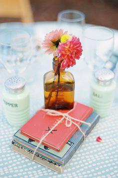 A stack of vintage reads is topped with a 'Watkins' bottle filled with colorful spring blooms.