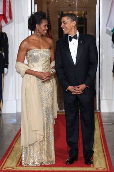 First Lady Michelle Obama is legendary for her gorgeous State Dinner gowns. For her first State Dinner in she stunned in a strapless, fitted gown by Indian-American designer Naeem Khan. This is what class looks like. Michelle Obama Fashion, Michelle And Barack Obama, Michelle Obama Vestidos, Barack Obama Family, Malia And Sasha, Gisele Bündchen, Lady, First Black President, Tilda Swinton