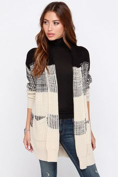 Fashion-forward and fabulously fine, the There and Back Again Black and Beige Sweater is sure to keep you covered on those cool mornings! Switching from black to beige, and throwing in chic chunks of stripes, this cable knit sweater wins ample style points. A shawl collar drapes into slim lapels, centered between two front patch pockets and long cuffed sleeves. Unlined. 72% Acrylic, 28% Cotton. Hand Wash Cold. Imported.