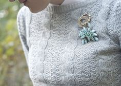 cluster of brooches on a cable knit sweater