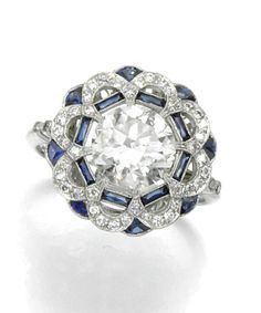 Sapphire and diamond ring. Set to the centre with a circular-cut diamond, within an open work border millegrain-set with calibré-cut sapphires and circular-cut diamonds, to a pierced gallery, French import marks.