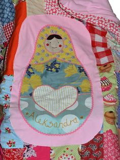 This is a quilt made by me from sections of old clothing with an applique Russian doll motif in the centre. It is lined with pink fleecy fabric and filled with wadding. It was made for a very lucky little girl :) KeShuni