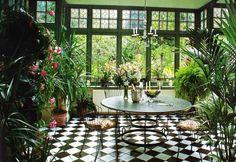 jardin d'hiver avec table ronde, sol à damier et lustre ancien