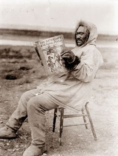 Description: 1913 photo Eskimo reading Saturday Evening Post in the arctic region graphic. Photograph shows an Eskimo wearing an anorak and heavy gloves sitting on a stool in an open field reading the Saturday Evening Post.