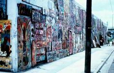 "His first major work was a self-initiated effort. Beginning in 1973 Young attached hundreds of painted panels to a wall of dilapidated buildings on a street of Overtown, a few blocks north of downtown Miami. The wall, ""Goodbread Alley"" developed over a period of two years, veiling, with an atmosphere of a circus, the harsher reality of the ghetto surrounding it."
