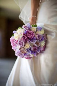 Soft and romantic.  This bridal bouquet is a mix of delicate shades of ivory and lavender.  The flowers include roses in shades of lavender and ivory.  Then we added orchids and sweetpeas for additional softness.  The image was beautiful captured by Jacqueline Photography -