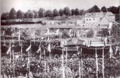 Grundsteinlegung am 15. Mai 1865. Es sind ein Festzelt und eine Ansammlung von Menschen zu erkennen. Es sind viele Fahnen aufgestellt. Im Hintergrund ist die Aachener Stadtmauer zu erkennen.