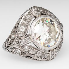 ART DECO 3 CARAT TRANSITIONAL CUT DIAMOND ENGAGEMENT RING PLATINUM. This magnificent antique engagement ring is centered with a 3.03 carat transitional cut diamond grading M / SI1 set into a fabulous art deco mounting. The bezel set center diamond sits in a pierced gallery with etched and carved floral designs. Accenting the main diamond is a halo of round Old European and square French cut diamonds finished with milgrain edging.