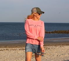 Love this casual look. Pink sweater, denim shorts, sneakers, and baseball hat.