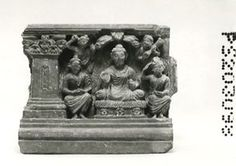 Panel showing the Buddha flanked by seated figures. Beneath three leafy branches the Buddha is seated in abhaya on a rectangular seat with a simple plinth, three four-petalled rosettes on its face and what looks like a high grass cushion. The robe shows dense folds, mainly in ridges, and below the loop in the Buddha's raised left hand gathered drapery spreads down to the seat.
