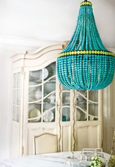 Love this bright burst of turquoise in this eclectic chandelier amongst a room full of white. Such a fun pop of color.