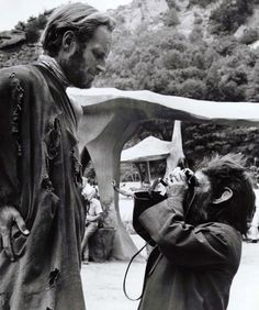 Charlton Heston being photographed by an ape on the set of Planet of the Apes