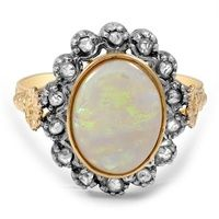 A Victorian-era treasure, this 14K yellow gold ring features a mesmerizing opal cabochon accented by cushion shaped natural purple sapphires and four rose cut diamonds (approx. 0.02 total carat weight).