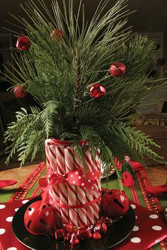 Christmas centerpiece with candy cane sticks and greenery spinkled with a few red bulbs all tied with festive ribbon...simply perfect.