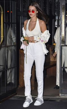 Bella Hadid rocks and all-white ensemble making the red colored lenses of her round shades POP!