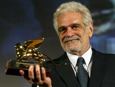 """Egyptian actor Omar Sharif holds up the Golden Lion lifetime achievment award at the Venice Film Festival August 29, 2003. Sharif, who stars in French director Francois Dupeyron's new film """"Monsieur Ibrahim et les fleurs du Coran"""" (""""Mr. Ibrahim and the Flowers of the Koran"""") premiering at the 60th edition of the festival, said the event marked a """"comeback"""" for him. REUTERS/Tony Gentile TG/FMS - RTR2ATT"""