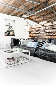 Black Ligne Roset couch, wood shelves and rafters. HKliving