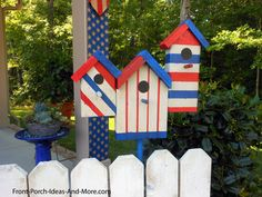 Darling birdhouses painted for the 4th of July look cute on the picket fence. Front-Porch-Ideas-and-More.com #porchideas #patrioticporches