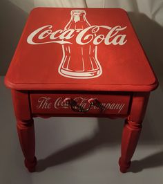 This piece has been transformed into a very unique and classic looking Coca-Cola end table. The table was sanded down and painted red before adding the custom hand painted Coca-Cola logos. The table is solid wood and features a pair of Coca-Cola bottle caps on the drawer pull handle. If you have a Coke lover or collector in your life, then this piece would make a great addition for them.     Priced at $139.00    Local pickup only unless buyer arranges shipping.      Shop this product…