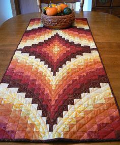 The colors on this quilted table runner make the perfect fall addition to your décor. It also makes a wonderful gift. I machine quilted it with a lovely burnt orange thread in a beautiful diamond pattern. The final photo show the back of the quilt which is almost as lovely as the front.    Machine wash cold, machine dry, iron as needed.  It measures 19 x 49    All my pieces include free shipping within the continental United States.