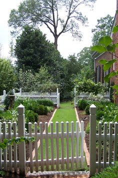 Nice manicured garden with raised beds., White fence.